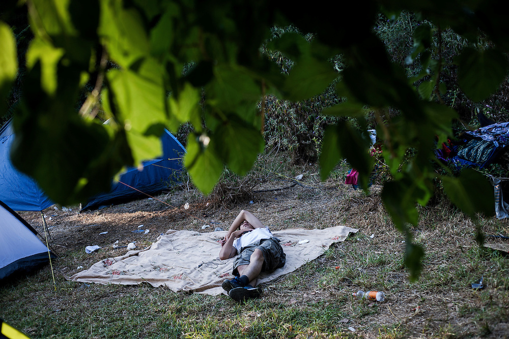 Greece, Athens, July 25th 2015 - A man is slipping on the ground at Pedion tou Areos park where hundreds of migrants and refugees mostly from Afghanistan have build a temporary camp, after they arrived in Athens from the Greek islands wishing to continue their journey to central Europe.