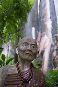 Statue of a monk at a temple with cave near Chiang Rai.
