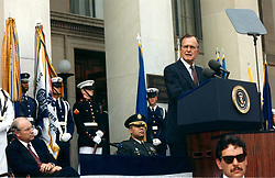 Washington, D.C. - August 15, 1990 -- United States Secretary of Defense Dick Cheney (seated left) and Chairman, Joint Chiefs of Staff, General Colin E. Powell, United States Army (seated center), listen as United States President George H.W. Bush delivers a speech to Pentagon employees, August 15, 1990. President Bush praised the Defense Department workers for their untiring efforts in support of the deployment of United States military forces to the Middle East -- Operation Desert Shield, and condemned President Saddam Hussein of Iraq for his invasion of Kuwait. Photo by White House/ CNP/ABACAPRESS.COM