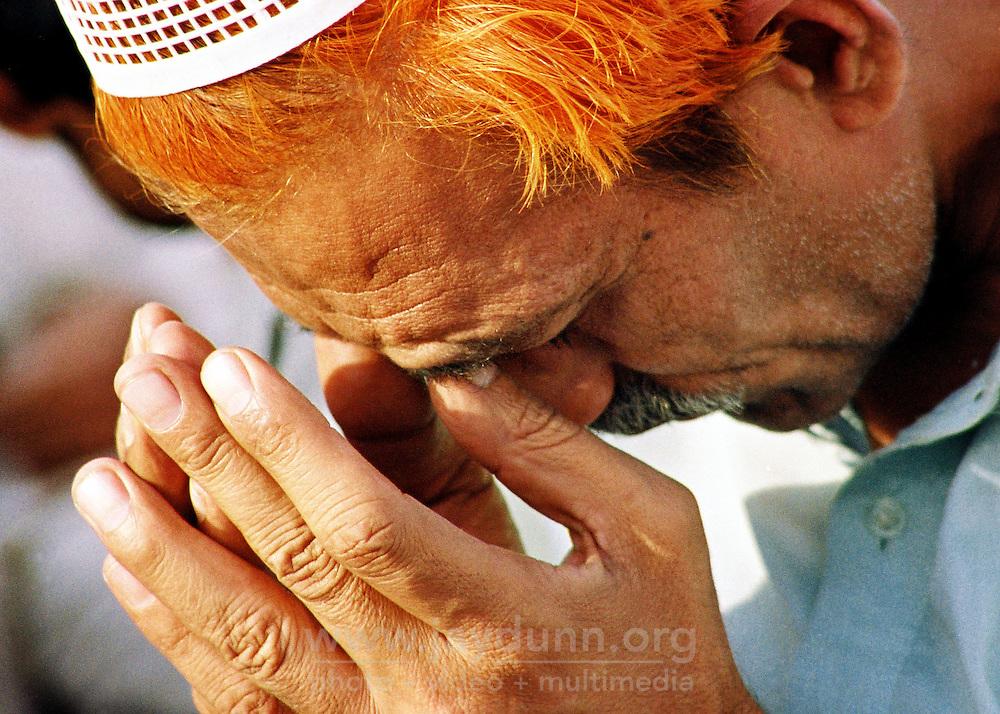Pakistan, Karachi, 2004. At central Karachi's beautiful domed Defense mosque, a Muslim man concentrates during Friday prayers.