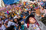 "13 JANUARY 2014 - BANGKOK, THAILAND: A Thai woman waves to a TV news helicopter during an anti-government protest in Bangkok. Tens of thousands of Thai anti-government protestors took to the streets of Bangkok Monday to shut down the Thai capitol. The protest was called ""Shutdown Bangkok"" and is expected to last at least a week. The Shutdown Bangkok protest is a continuation of protests that started in early November. There have been shootings almost every night at different protests sites around Bangkok, including two Sunday night, but the protests Monday were peaceful. The malls in Bangkok stayed open Monday but many other businesses closed for the day and mass transit was swamped with both protestors and people who had to use mass transit because the roads were blocked.    PHOTO BY JACK KURTZ"