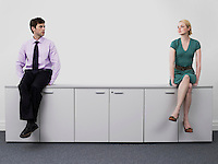 Young male and female business people sitting on office cabinets