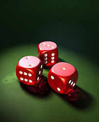 3 Red Dice on a green felt surface in a spot