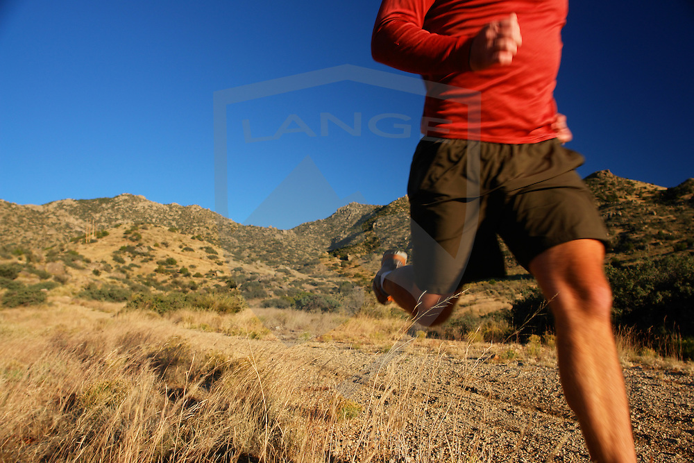 trail runner man and mountain landscape.  sandia mountains, new mexico.