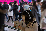 A young Japanese woman loses herself in her ipad screen among the crowds in Hachiko Square, Shibuya, Tokyo, Japan. Sunday January 12th 2020
