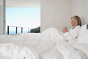 Mature woman in bathrobe holding cup lying in bed side view