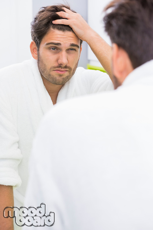 Reflection of man suffering from headache in mirror
