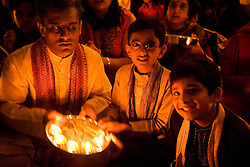 Man and boys worshipping by candlelight in celebration of Navratri; the Hindu festival of Nine Nights,