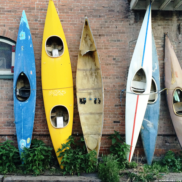 A colorful row of old, vintage kayaks decorate an alleyway in downtown Salida, Colorado.