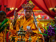 04 SEPTEMBER 2017 - BANGKOK, THAILAND: A Chinese Buddhist monk leads a prayer at Chaomae Thapthim Shrine. About 1,000 people came to the shrine for the annual food distribution. Staples, like rice and cooking oil, are donated to the shrine throughout the year and donated to poor people from the communities around the shrine. Food distributions like this are a tradition at Chinese shrines in Bangkok and a common way of making merit for the people who donate the staples.     PHOTO BY JACK KURTZ