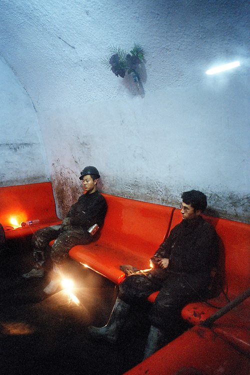 Deep inside a mine shaft coal miners rest in a waiting room. They wait for a train that will pick them up and drop them at a lift that will take them back up to the surface again. On average these workers are paid about 3000 RMB (£230) per month. Many of these workers suffer respiratory illneses at an early age. Datong, Shanxi, China.