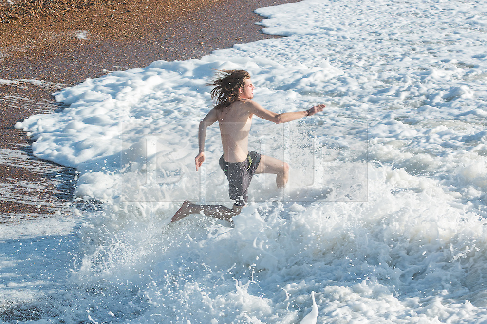 © Licensed to London News Pictures. 28/12/2015. Brighton, UK. 25 year old Brighton based Sebastian Pieper takes his monthly swim in the sea. People relax on Brighton beach as the weather turns increasingly warmer. Today December 28th 2015. Photo credit: Hugo Michiels/LNP