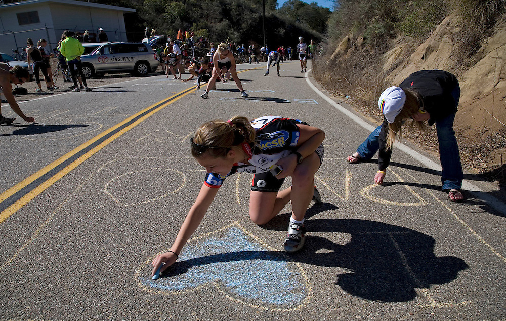 Whitney Wilkinson, 22, of the UCSB cycling team, center, and Sara Borowski, 22, of Los Gatos, right, use chalk to mark Highway 150 in Lake Casitas with supportive messages for riders in the Amgen Tour of California approach the second King of the Hill on Saturday morning.