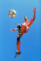 Male football player kicking ball, low angle view (blurred motion)