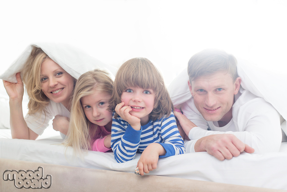 Portrait of happy parents and children lying under bed cover