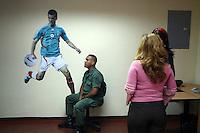 Fussball   International   42. Copa America   Feature           Im Buero fuer Presseakkreditierung sorgt ein Soldat fuer Sicherheit. An der Wand haengt ein Poster vom mexikanischen Nationalspieler BORGUETTI.