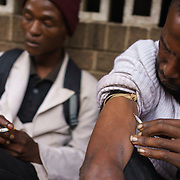 """Sfiso, a drug addict, using a visibly dirty shared needle to inject himslef with """"nyaope"""" on a street in Hillbrow, an inner-city neighbourhood in Johannesburg, South Africa that is plagued by drugs. A crude form of heroin reputedly cut with anything from anti-retrovirals to rat poison to pool cleaner, nyaope is cheap (about R20/ $1.70 per """"round"""") and devastatingly addictive - it produces a brief high, but then leaves the user with vicious withdrawal symptoms, constantly searching for the next high. It is said that a single dose is enough to result in addiction."""