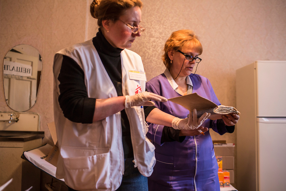 ZIMOGORYE, UKRAINE - MARCH 15, 2015: Lidia Grishko, left, a physician with Medecins Sans Frontieres, and Venera Lukyanchenko, right, a general practitioner at the Zimogoryivskaya Ambulatory, review a patient's documents in Zimogorye, Ukraine. CREDIT: Brendan Hoffman for The New York Times
