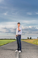 Portrait of serious young man making stop gesture at country road