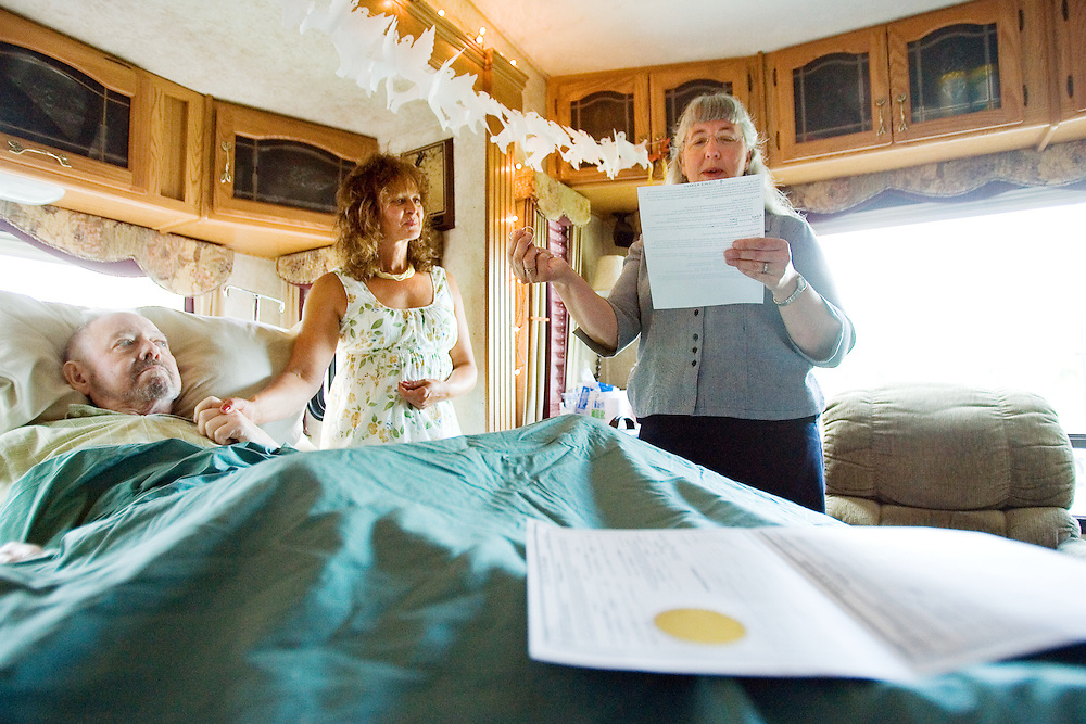 June 8 -- While Nancy and Dick clasp hands, Patty Bullick, a former Hospice of North Idaho social worker, performs a bedside wedding ceremony while holding their rings.