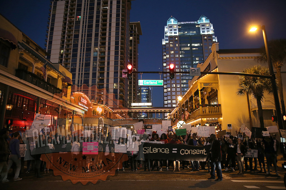 """Protesters march through downtown Orland0 to the Amway Arena, home of the Orlando Magic, to perform a """"die in"""" to rally against police brutality on Wednesday, December 10, 2014 in Orlando, Florida.  Since a Staten Island grand jury decided last week not to bring any charges against a white officer who was seen on video using a chokehold on Eric Garner, and other use of questionable force issues by the police across the country, the Orlando protesters wanted to represent the city of Orlando.  (AP Photo/Alex Menendez)"""