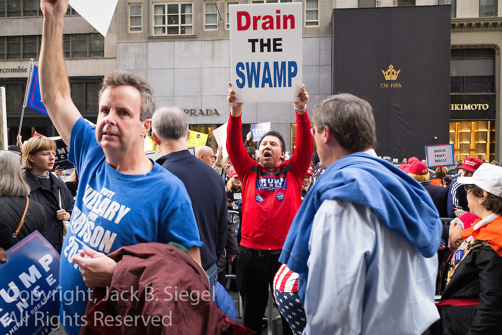 """A male supporter of Donald J. Trump holding a """"Drain the Swamp"""" sign at a gathering on New York's Fifth Avenue in front of Trump Tower the Saturday before the November 2017 election"""