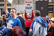 "A male supporter of Donald J. Trump holding a ""Drain the Swamp"" sign at a gathering on New York's Fifth Avenue in front of Trump Tower the Saturday before the November 2017 election"