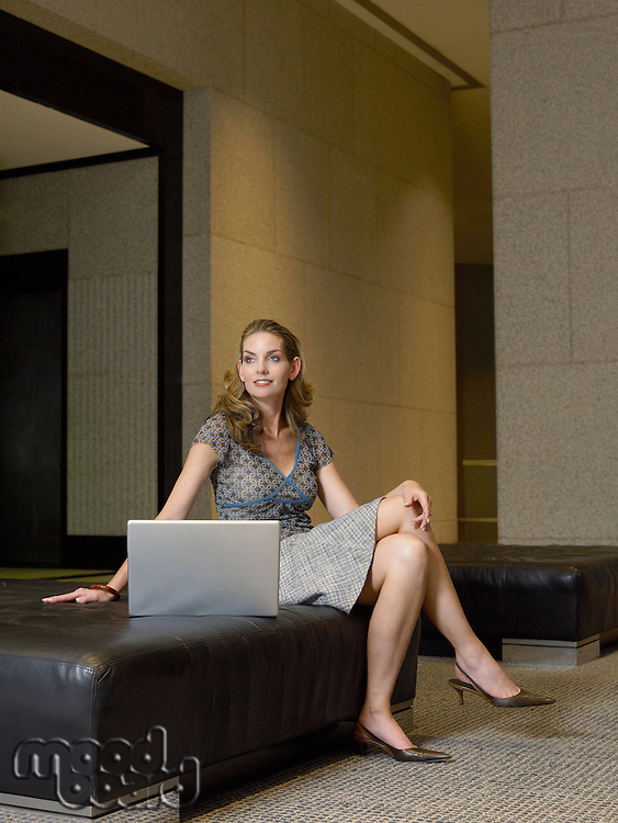 Woman with laptop in lobby