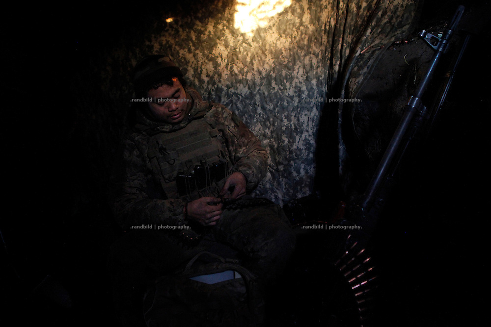 Charlie sits in dark machine gun position during sunset and load an ammunition belt.<br /> <br /> +++   +++ The Boom Stick Brotherhood +++   +++  <br /> <br /> Driven by a certain fascination on military and a simple shaped nationalistic ideology young men travel the world to fight at frontlines of recent conflicts. Five volunteering warriors from europe and the US were walking into battle in Ukraine last year. Ben, Alex, Craig, Charlie and Cowboy made it to the frontline joining the right-wing militia Right Sector (Prawji Sektor) to defend Ukraine by fighting seperatists and russian irregular forces aiming to split off the eastern Donbass region from the country.<br /> <br /> As ukrainian forces are short of servicemen Right Sector is welcomed to support the defense efforts at hotspots. Receiving no payments but shelter, food and ammonition the foreigners selfmade battlegroup Task Force Pluto found itself in a so called Anti-Terror-Operation close to the Donetsk Airport. Though Minsk II Agreement for Ceasefire is in effect several daily fire exchanges taking place between both conflict parties at the line of contact. However the war is now fought in a World War I alike stalemate in muddy trenches which were digged during the World War II.<br /> <br /> As a loose union of individuals the Boom Stick Brotherhood is no certain ukrainian phenomenon and not tied to the recent war only. If things would become boring, crazy or if the army leadership would deter foreigners from fighting Ben and his comrades would move on looking for another destination around the globe to be involved in battle. That&acute;s what they are aiming for. They are living a dream of smoking guns, camaraderie and a simple outdoor life. A lifestyle devoted to look every day into the ugly face of death.<br /> <br /> The Boom Stick Brotherhood is a multi-national, multi-religious and multi-ethnic group of men in its twenties:<br /> Ben, an austrian infantryman travelling to hot zones since years. Bore