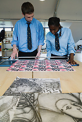 Secondary school students using a guillotine to cut paper in art lesson,