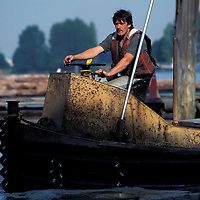 "Canada, British Columbia, Tim McKernan pilots a ""Winder Boat"" sorting floating logs at Delta Cedar Products in Vancouver"