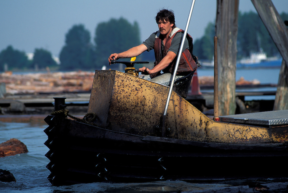 """Canada, British Columbia, Tim McKernan pilots a """"Winder Boat"""" sorting floating logs at Delta Cedar Products in Vancouver"""