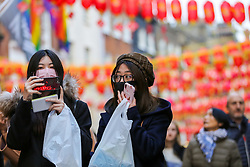 © Licensed to London News Pictures. 25/01/2020. London, UK. Women wearing face masks as a precaution against the outbreak of the Coronavirus, during Chinese New Year celebrations in London's Chinatown. Photo credit: Dinendra Haria/LNP