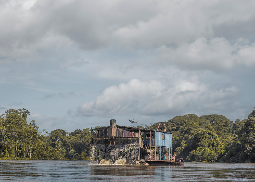 Grand-Santi, Maroni, 2015.<br /> <br /> Barge d&rsquo;orpaillage face &agrave; la commune de Grand-Santi. Depuis les efforts entrepris par le gouvernement fran&ccedil;ais pour juguler l&rsquo;orpaillage clandestin dans l&rsquo;Ouest guyanais, les barges qui avaient pratiquement disparues r&eacute;apparaissent sur le Maroni, fleuve frontalier du Suriname. Les pompes de cette embarcation aspirent le fond du fleuve &agrave; la recherche d&lsquo;or alluvionnaire. L'embarcation poss&egrave;de trois chambres climatis&eacute;es, une cuisini&egrave;re Surinamaise et quatre ouvriers br&eacute;siliens assurent le bon fonctionnement du travail. La mouvance des eaux et la mobilit&eacute; du proc&eacute;d&eacute; rendent difficilement contr&ocirc;lable ce travail de l&rsquo;or &agrave; la fronti&egrave;re de la l&eacute;galit&eacute;. <br /> <br /> La convention de Paris sign&eacute;e entre la France et les Pays-Bas le 30 septembre 1915 stipule que &laquo; la fronti&egrave;re entre la France et le Suriname est pr&eacute;cis&eacute;ment d&eacute;limit&eacute;e entre l&rsquo;&icirc;le Portal (proche de Saint-Laurent du Maroni) et l&rsquo;&icirc;le Stoelman (plus haut sur le Maroni) par la ligne m&eacute;diane du fleuve Maroni. Cette convention de 1915 &eacute;tablit &eacute;galement &laquo; un r&eacute;gime de libert&eacute; de navigation sur cette portion du fleuve. Les contr&ocirc;les de police aux fins de pr&eacute;vention ou de r&eacute;pression d&rsquo;infractions p&eacute;nales y sont licites dans la mesure o&ugrave; ils n&rsquo;entravent pas sans justification cette libert&eacute; &raquo;. Dans les faits, sur les eaux mouvantes du Maroni, il n&rsquo;existe pas de d&eacute;limitation conventionnelle de l&rsquo;emplacement exact de la fronti&egrave;re dans le lit du fleuve qui ne soit contestable.<br /> <br /> Strictement interdites en France mais tol&eacute;r&eacute;es de l&rsquo;autre c&ocirc;t&eacute; de la fronti&egrave;re, une trentaine de barges sont recens&eacute;es le