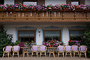 Pink cushions on wicker seats outside a rural hotel in the Dolomites town of Badia-Abtei, Italy.