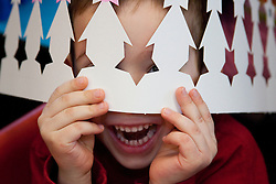 United States, Washington, Bellevue, boy (age 4) holding paper crown over eyes.  MR