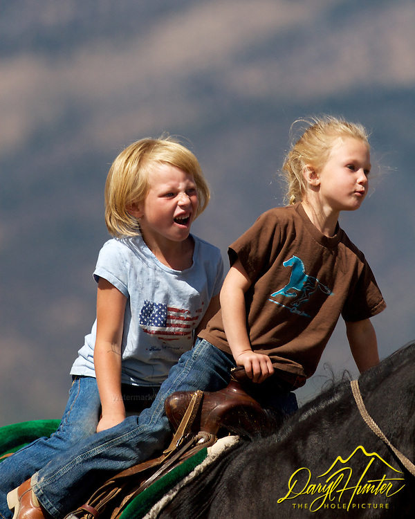 Ranch kids, young cowgirls riding double on horse, having the time of their life in Swan Valley Idaho