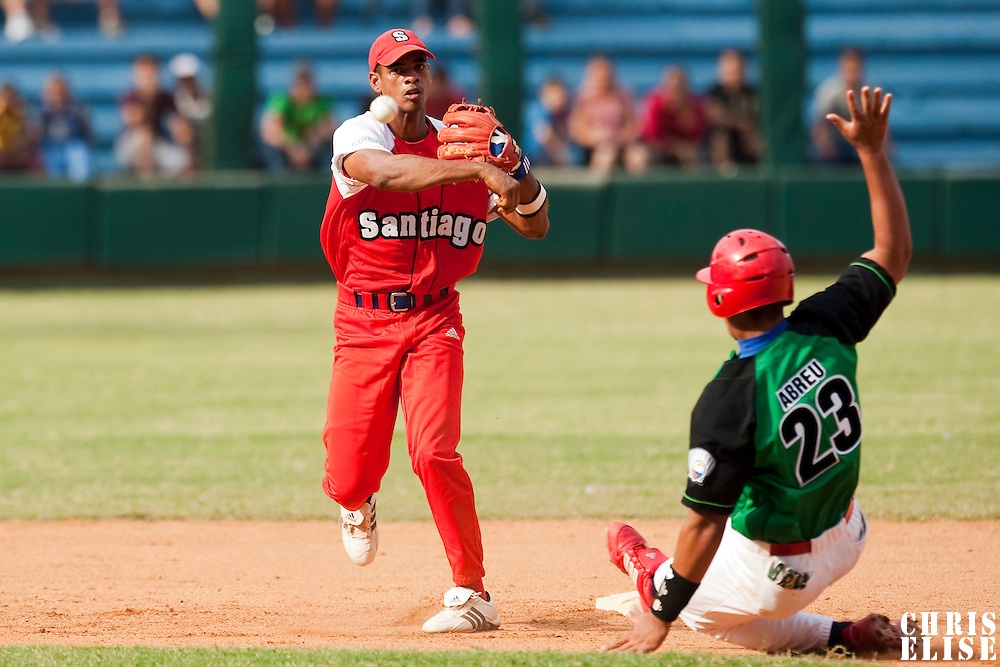 15 February 2009: Second base Hector Olivera of the Orientales throws the ball to first base for a double play during a training game of Cuba Baseball Team for the World Baseball Classic 2009. The national team is pitted against itself, divided in two teams called the Occidentales and the Orientales. The Orientales win 12-8, at the Latinoamericano stadium, in la Habana, Cuba.