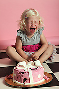 young blonde girl of two crying over a half eaten birthday cake Model release available