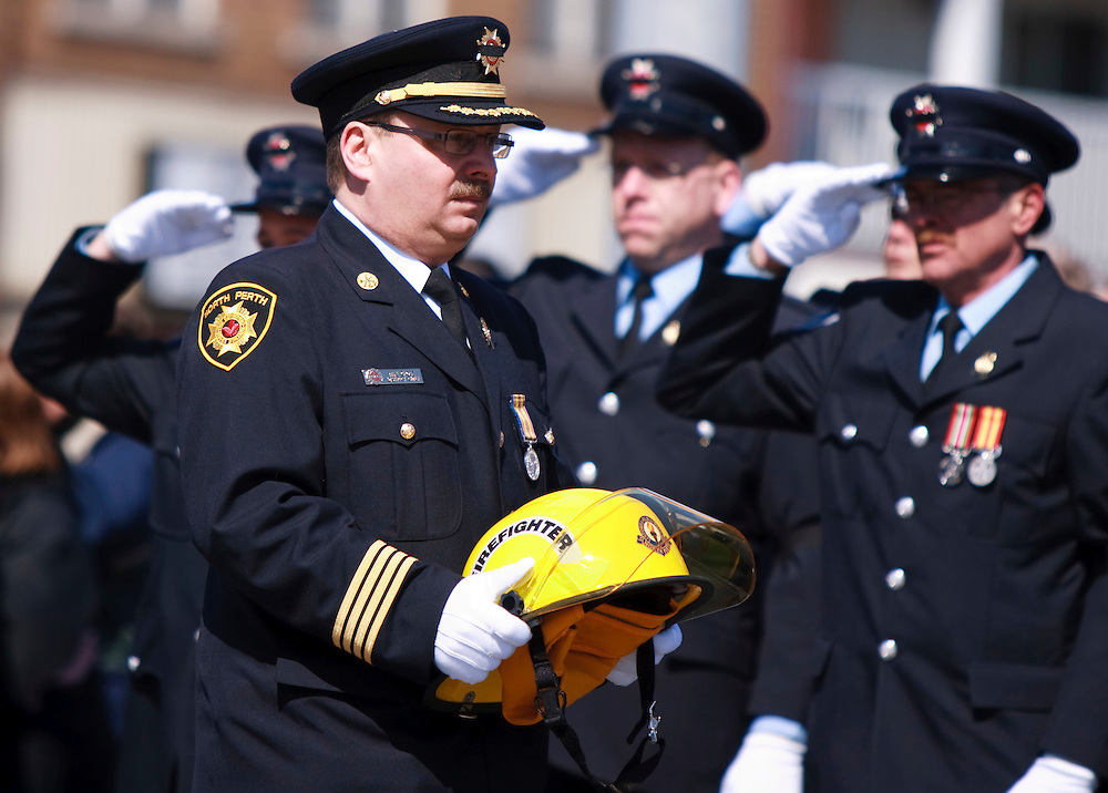 North Perth Fire department District chief Mike Ghesz carries the helmet of fallen colleague Kenneth Rea during a funeral procession in Listowel Ontario, for Rae and Raymond Walter Thursday, March 24, 2011.THe men were killed fighting a blaze in a dollar store last Thursday when the roof collapsed.<br /> THE CANADIAN PRESS/ Geoff Robins