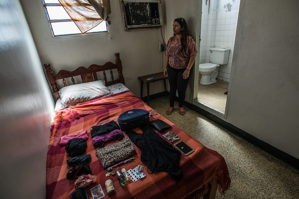 LA VELA, VENEZUELA - SEPTEMBER 23, 2016: Irene Poza poses for a portrait with the few items that she will take with her when she is smuggled to Curaçao from Venezuela.  Ms. Poza used to work as a secretary for PDVSA, the state oil company - but lost her job when oil prices fell and the Venezuelan economy started to spiral out of control. Her family's situation is so bad, they struggle to buy enough to eat, and her mother has a heart condition and the family struggles to find the medicines that she needs.  So Irene decided to pay smugglers to take her to Curaçao where she will work cleaning a fast food restaurant and a nightclub. Her situation makes her very angry. She studied hard, and did everything young people are supposed to do to get a good job, she said. In Curaçao she can make in one day cleaning as much money as she would make all month working in a PDVSA office.  She had to stay in this motel because she had to lie to her parents and tell them she was staying with a friend - she said if her mother knew what she was doing, she was afraid the stress would make her heart condition worse. PHOTO: Meridith Kohut for The New York Times