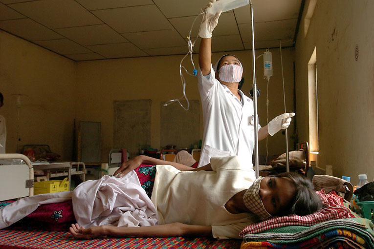 Cambodia. Takhmao, Kandal (near Phnom Penh). 2006. A nurse at Chey Chumneas Hospital in Takhmao, Kandal changes an IV drip bottle for an HIV patient suffering from TB.