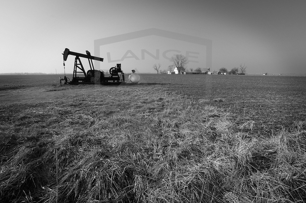 indiana rural oil rig meadow and distant farmhouse, black and white, horizontal, copy space