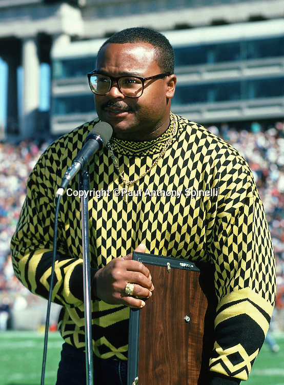 Former Chicago Bears linebacker Mike Singletary speaks into the public address microphone as he is honored at halftime of the Chicago Bears NFL football game against the Atlanta Falcons on Oct. 3, 1993 in Chicago. The Bears won the game 6-0. (©Paul Anthony Spinelli)