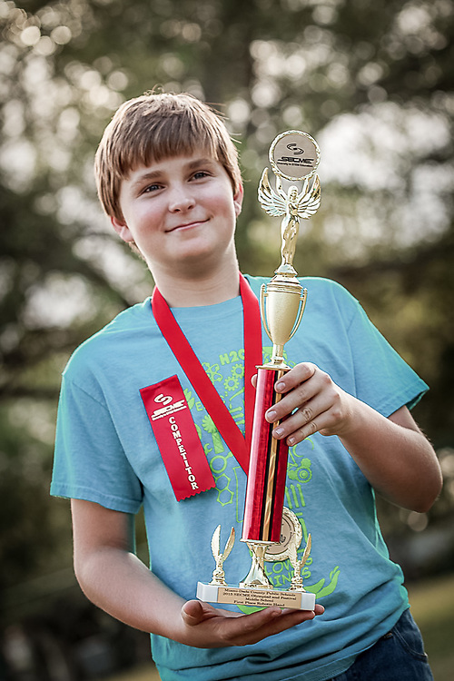 boy with trophy and ribbons