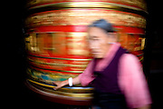 Kathmandu. A devotee walks around the prayer wheel at a buddhist monastery on the outskirts of the city.