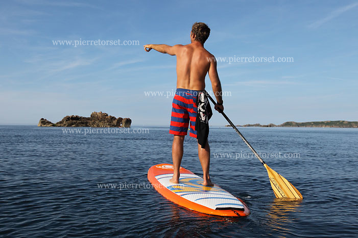 Brittany, France. Discover a new sea activity along the seaside of Brittany : the Stand Up Paddle. Standing up on a very stable board, you paddle to move forward. It is the perfect activity for people eager to discover the costline from another perspective, wuithout having any surfing experience. Just a bit of balance is required, and it can fit for the whole family.