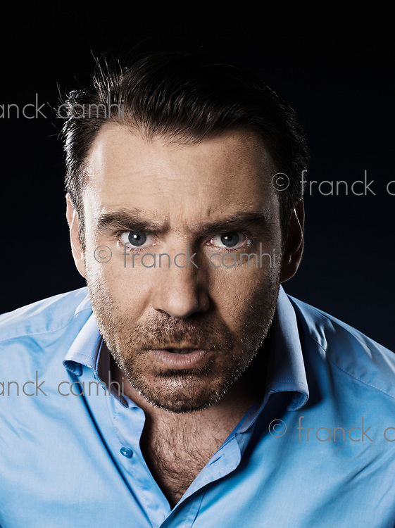 one caucasian man unshaven angry portrait looking at camera isolated studio on black background