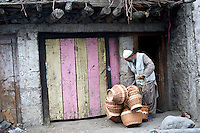 A basket seller retrieves some more baskets from his storage shed in Kargil