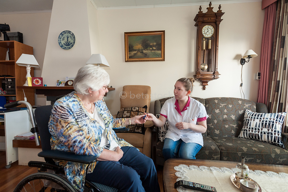 Homecare nurse and patient injecting diabetes medicine at home. Verpleegkundige en thuiszorg patient prikken samen een diabetes prik.